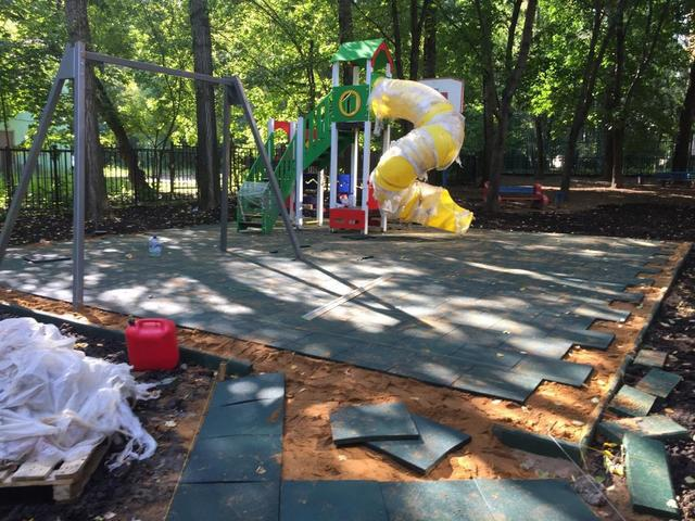 На детской площадке во дворе на Академика Королева коммунальщики укладывают резиновые плиты